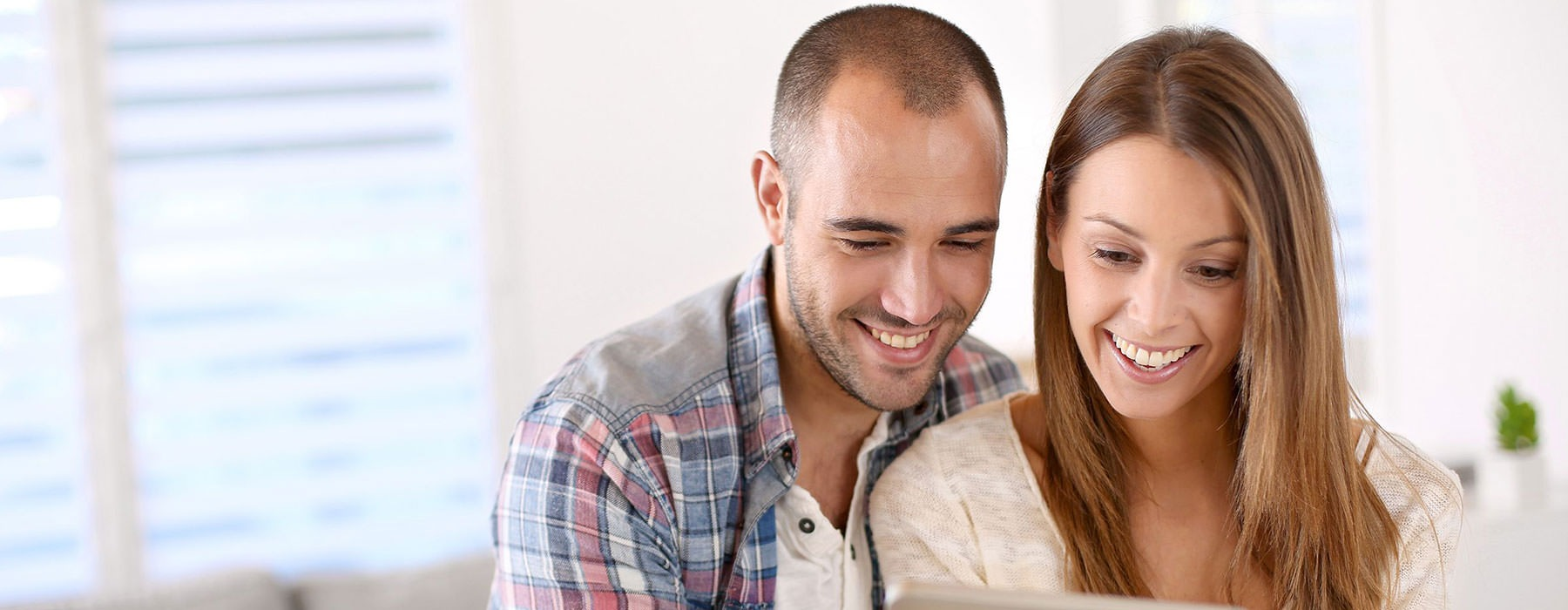 lifestyle image of a couple looking at a smart tablet together